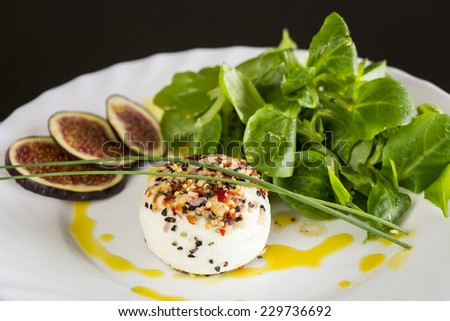 Delicious appetizer of seasoned goats milk cheese with fresh ripe sliced figs and leafy green herb salad served on a plate - stock photo