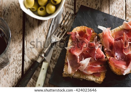 Delicious appetizer of spanish ham and salad, on rustic table - stock photo