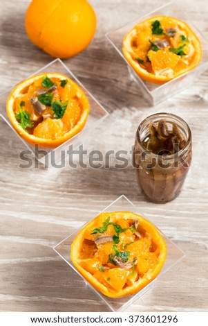 delicious appetizer with orange and anchovy fillet inside  half  - stock photo