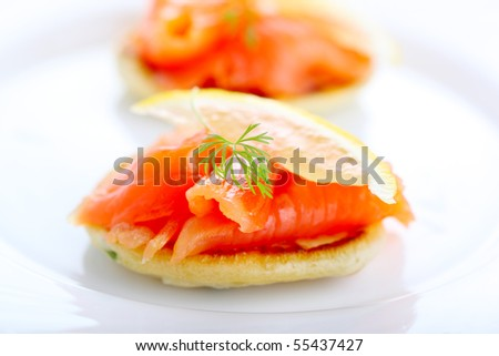 delicious appetizer with salmon pancakes and lemon - stock photo