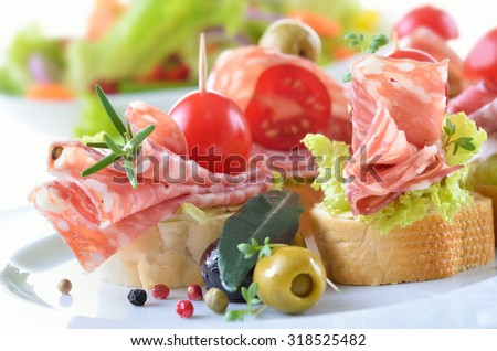 Delicious appetizers with Italian salami, lettuce leaf and cherry tomato on a  slice of baguette - stock photo