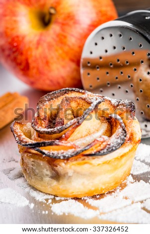 Delicious apple cakes with sugar on kitchen table. - stock photo