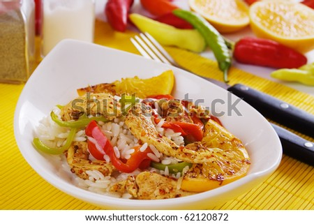 Delicious asian spicy chicken meat with rice, vegetables and fried orange
