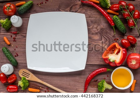 Delicious Assorted fresh vegetable, tomato, cucumber, pepper, carrot - healthy food, diet or cooking concept. White plate for text. - stock photo
