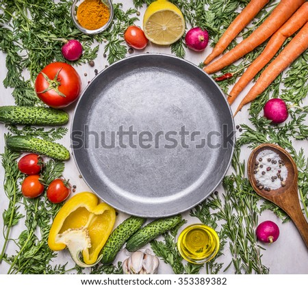 Delicious assortment of farm fresh vegetables, cucumbers, peppers, lemon, cherry tomatoes, oil, salt spoon laid out around the pan on wooden rustic background top view close up - stock photo
