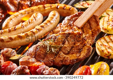 Delicious assortment of meat neck steak and vegetables grilling on a BBQ with pork sausages, chops, skewers with mixed kebabs, bell pepper and eggplant in a close up view with tongs turning a cutlet - stock photo