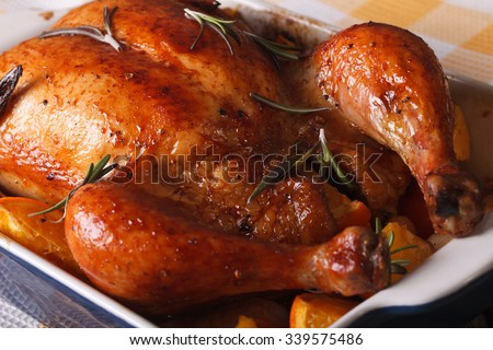 Delicious baked chicken with oranges in the baking dish on a table close-up. horizontal - stock photo