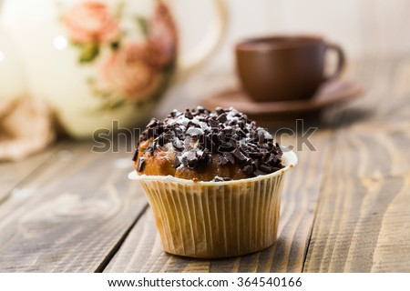 Delicious baked cupcake with chocolate crust for tasty breakfast and lunch on background of beautiful teapot and brown cup and saucer on wooden table indoor closeup, horizontal picture  - stock photo