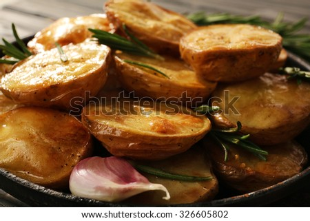 Delicious baked potato with rosemary in frying pan close up - stock photo