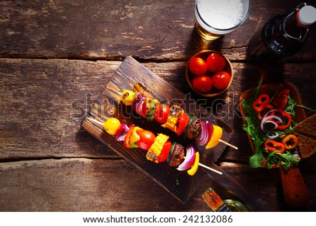 Delicious bar lunch of fresh vegan or vegetarian kebabs with assorted roasted colorful vegetables on skewers served on a rustic wood table with a beer and salad, with copyspace - stock photo