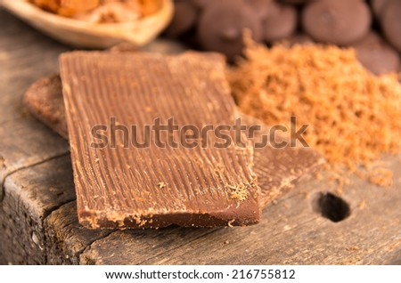 Delicious bar of milk chocolate and shredded chocolate on a wooden table selective focus - stock photo