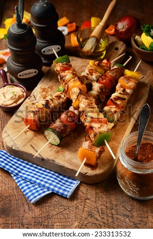 Delicious barbecued or grilled meat kebabs with onion and colorful bell pepper on a rustic wooden board surrounded by ingredients, marinade and seasoning - stock photo