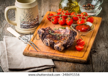 Delicious barbecued ribs seasoned with a spicy sauce and served with beer, seasonings, tomato and ketchup on an old rustic wooden chopping board - stock photo