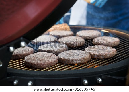 Delicious beef burgers cooking on a barbecue