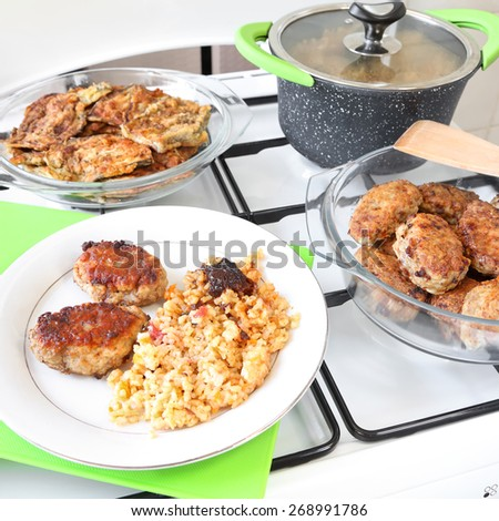 Delicious beef meatballs and asian rice with carrot and dried fruits served on a white plate.Eggplants baked in flour in the blurred background. Homemade cooking. Selective focus          - stock photo