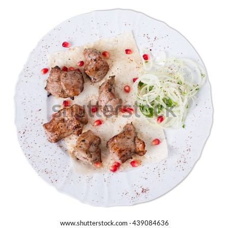 Delicious beef shish kebab on pita with onions and pomegranate seeds. Isolated on a white background.