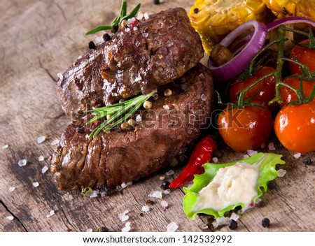 Delicious beef steak on wooden table - stock photo