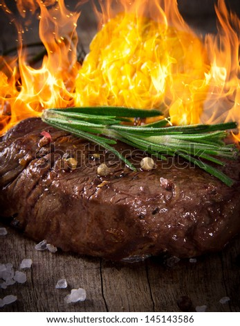 Delicious beef steak on wooden table with fire flames - stock photo