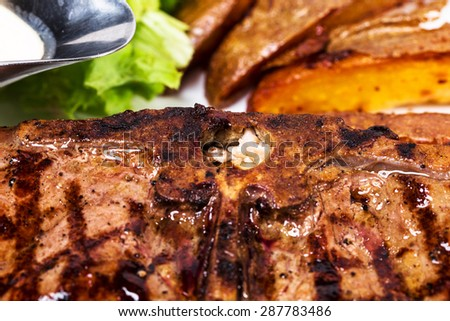 Delicious beef steak with roasted potatoes. Macro. Photo can be used as a whole background.
