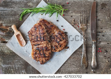 Delicious beef steak with rosemary on a old wooden board - stock photo