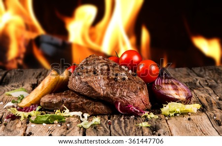 Delicious beef steakes on wood with fire background