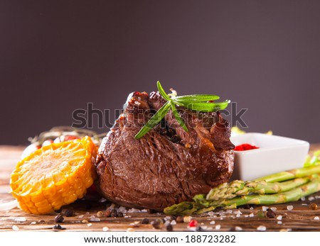 Delicious beef steaks with fresh vegetable and trimmings on wooden table. - stock photo
