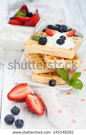 Delicious Belgian waffle with fresh berries and cream for breakfast - stock photo