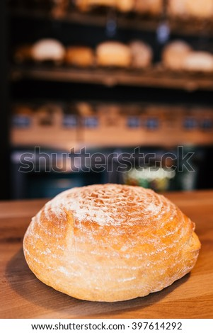 Delicious big round bread on wooden table  - stock photo