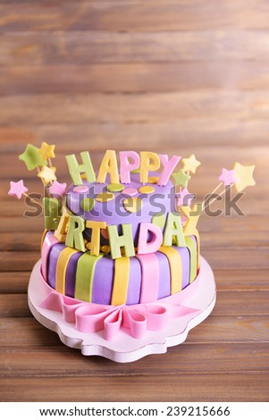 Delicious birthday cake on table on wooden background