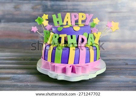 Delicious birthday cake on wooden background - stock photo