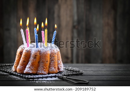 delicious birthday cake with colorful candles on dark background - stock photo