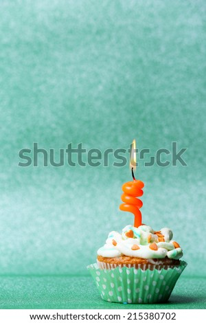 Delicious birthday cupcake on green background - stock photo
