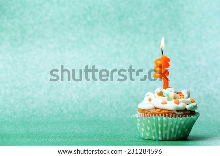 Delicious birthday cupcake on green background - stock photo