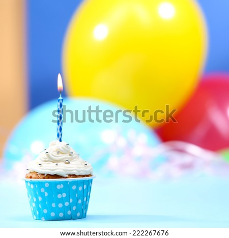 Delicious birthday cupcake on table on bright background - stock photo