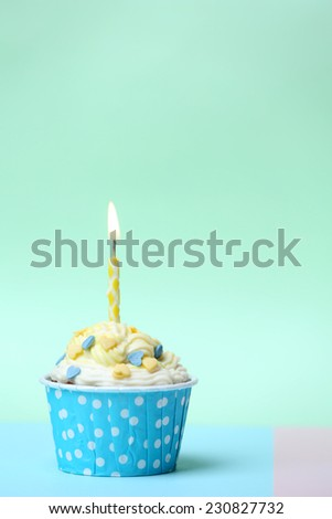 Delicious birthday cupcake on table on light green background - stock photo