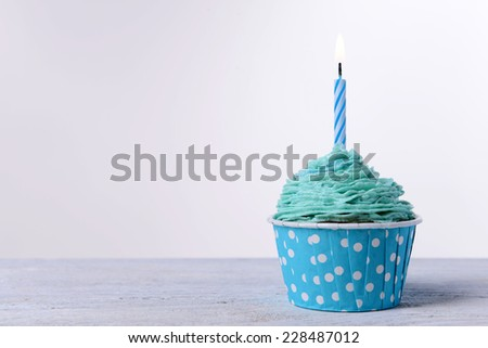 Delicious birthday cupcake on table on white background - stock photo