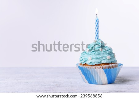 Delicious birthday cupcake on table on white background