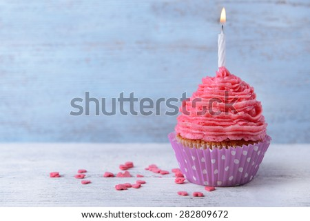 Delicious birthday cupcake on wooden background - stock photo