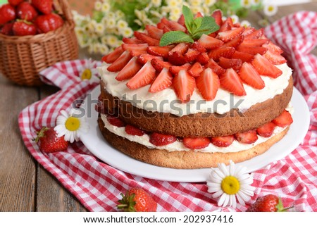 Delicious biscuit cake with strawberries on table close-up - stock photo