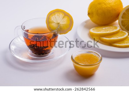 Delicious black tea in glass cup with lemon and honey. - stock photo