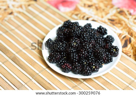 Delicious blackberry on a white plate - stock photo