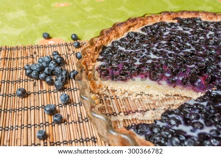 Delicious blueberry pie on the table with cutting pie in glass baking dish.  - stock photo