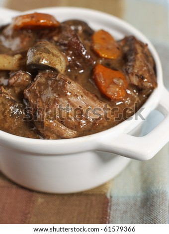 Delicious bourguignon beef stew in a small white bowl. Very Shallow depth of field. - stock photo