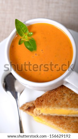 Delicious bowl of homemade tomato soup with a grilled cheese sandwich - stock photo