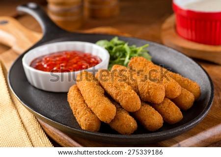 Delicious breaded mozzarella cheese sticks with marinara dipping sauce. - stock photo