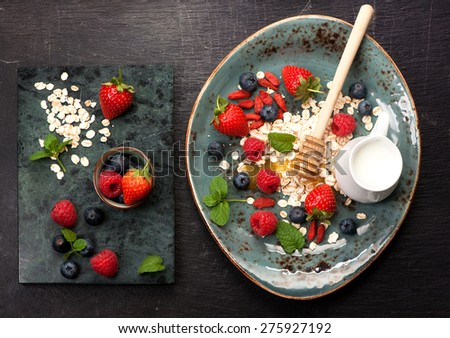 Delicious breakfast oatmeal,  berries, honey and milk. top view - stock photo