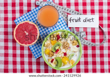 Delicious breakfast: oatmeal with fruit and yogurt. Bananas, citrus fruits, kiwi, apple, walnut - a healthy and nutritious breakfast. Fruit with yogurt and a glass of fresh juice for breakfast. - stock photo
