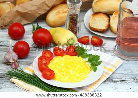 Delicious breakfast of scrambled eggs, baguettes  and vegetable on the plate