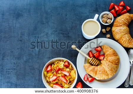 Delicious breakfast table with corn flakes, fresh croissants, honey, ripe strawberry and coffee, border, top view. Health and diet concept. Vintage background with space for text. - stock photo