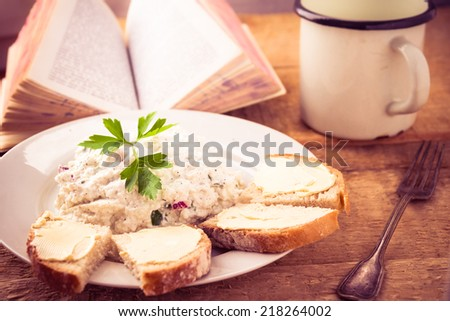 Delicious breakfast with a book on the kitchen table - stock photo